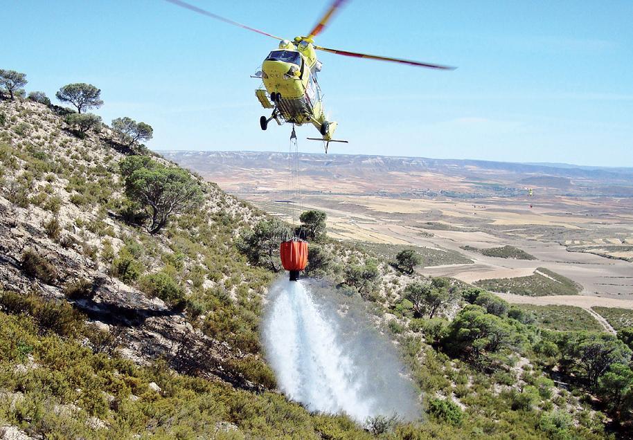 El helicóptero con base en Ejea actuando en un incendio con la ayuda del bambi desde donde descarga el agua. FOTO: B. HELITRANSPORTADA
